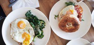 בראנץ' מושלם ב-SAM: מימין בייגל עם ביצת עין ובייקון; משמאל ביצים עם תרד מוקרם על טוסט